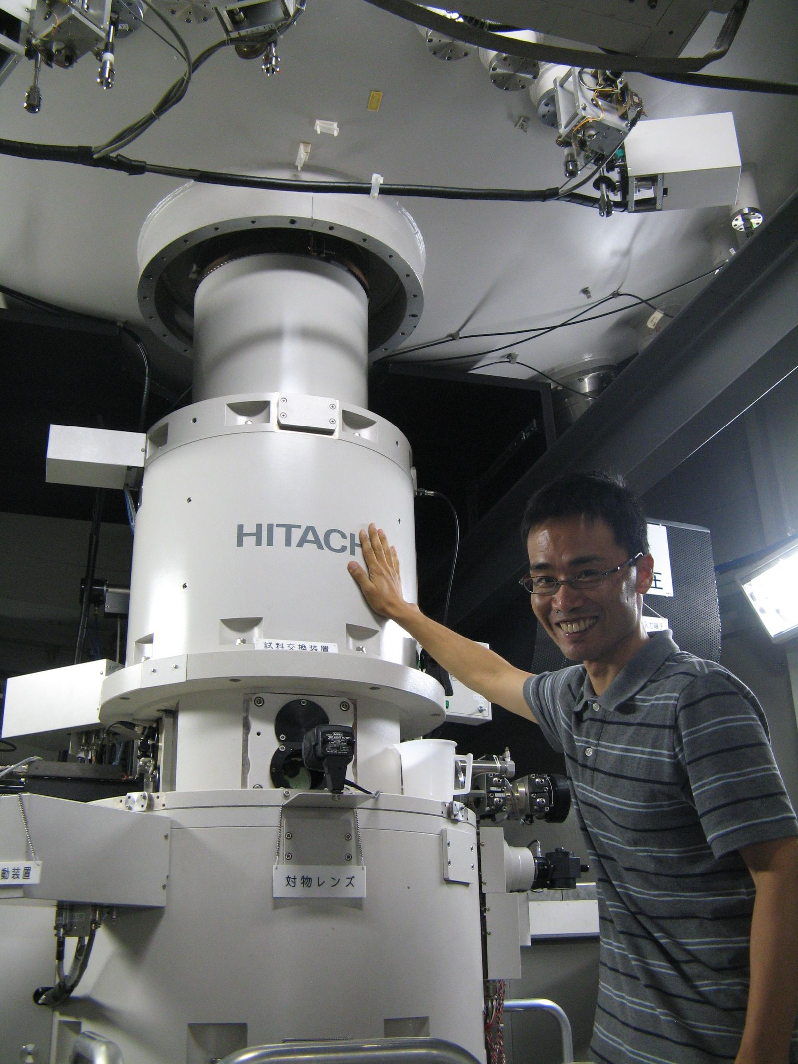 Professor Arakawa next to a High Voltage Electron Microscope