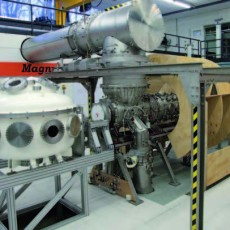 The fifteen meters long experiment Magnum- PSI. The white chamber on the left hand side is the in-vacuo analysis chamber, which will dock onto the target chamber enclosed by the wooden mock-up of the future superconducting magnet. The manipulator arm carrying the wall material will reach through the analysis chamber into the target chamber. Credit: FOM Institute for Plasma Physics Rijnhuizen