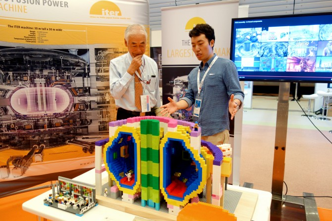 Former ITER Director-General Osamu Motojima visits the ITER stand, where a highly realistic Lego model of the ITER Tokamak is on display. Two students from Kyoto University (Konishi Laboratory, Institute of Advanced Energy) are brains behind this beauty—Taishi Sugiyama and Kaishi Sakane. Picture: ITER Organization